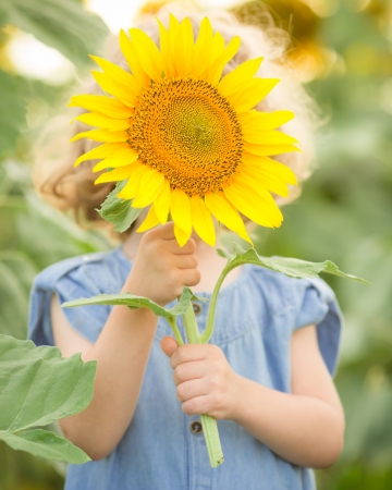 environmental protection: Happy child playing with sunflower in spring field Stock Photo