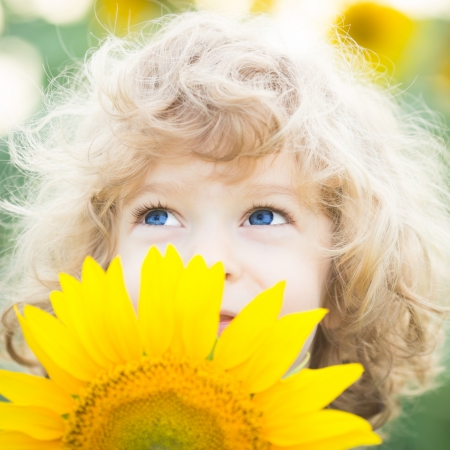Beautiful child with sunflower in spring field photo