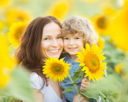 Happy family in spring field of beautiful sunflowers photo