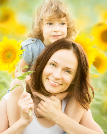 nature protection: Happy family in spring field of beautiful sunflowers Stock Photo
