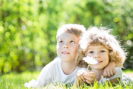 ni�os felices: Ni�os felices que mienten al aire libre en el parque del resorte Foto de archivo