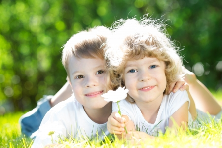 Girl and boy lying on green grass in spring park Stock Photo - 17500573