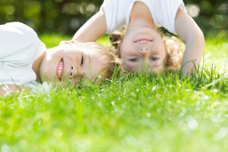 child couple: Happy children playing on green grass in spring park. Environment protection concept