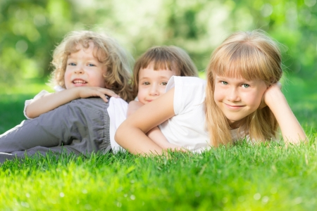 Happy children lying on green grass in spring park Stock Photo - 17500545