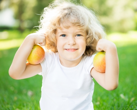 exersice: Happy child playing with apples outdoors in spring park. Fitness concept Stock Photo