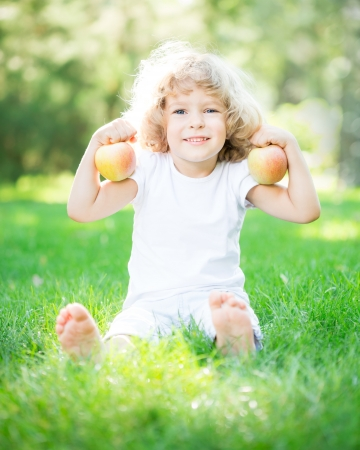 Happy child with apples sitting on green grass in spring park. Healthy lifestyle photo
