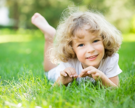 lying on grass: Happy child playing on green grass in spring park