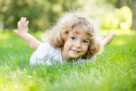 exersice: Happy child playing on green grass in spring