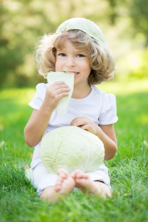 Happy child eating cabbage against green spring background photo