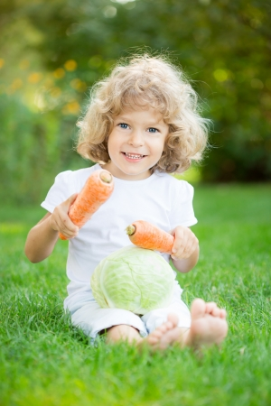 Happy smiling child with vegetables sitting on green grass in spring park  Healthy lifestyles concept photo