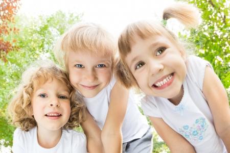 niños felices: Ángulo de visión baja retrato de niños felices que juegan al aire libre en la primavera de parque Fisheye disparo
