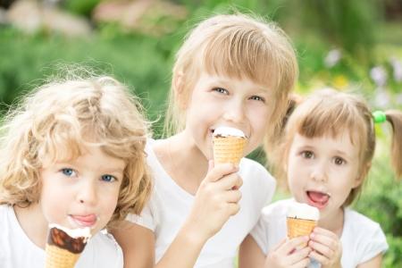 ni�os comiendo: Ni�os felices comiendo helado al aire libre en el parque