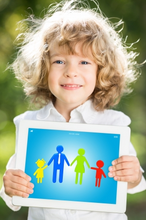 Happy child holding tablet PC with 3d family against green spring background photo