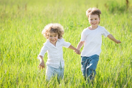 Happy children playing in spring field photo