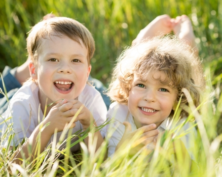 Happy children lying on grass in spring field photo
