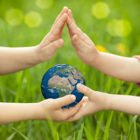 children holding hands: Earth in children s hands against green spring background  Elements of this image furnished by NASA