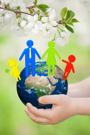 Earth with 3d family in children s hands against green spring background  Elements of this image furnished by NASA photo