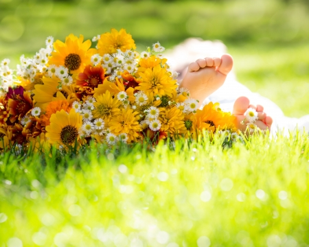 baby's feet: Healthy baby`s feet on green grass and spring flowers