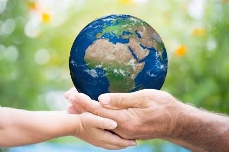 environmental protection: Child and senior man holding planet Earth in hands against green spring background.