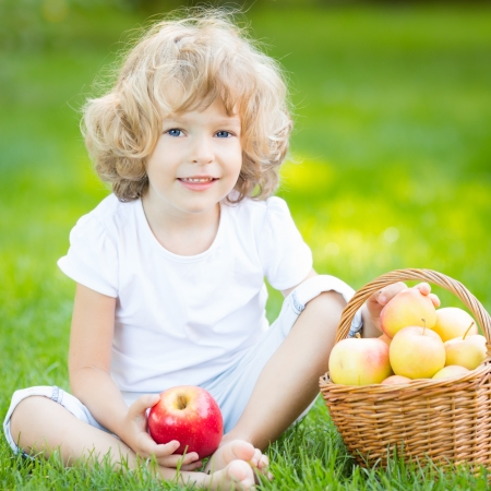 Happy child eating apple outdoors in spring park photo