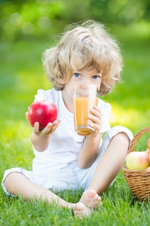 Happy child drinking apple juice in park against green spring background photo