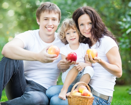 Happy family eating apples outdoors in spring park. Healthy lifestyle concept photo