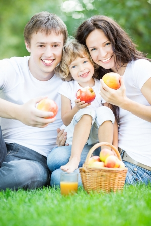 family health: Happy family sitting on green grass and drinking apple juice in spring park Stock Photo