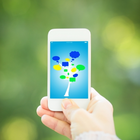 Woman hand holding smart phone against spring green background Stock Photo - 17546609