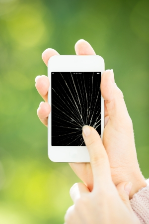 Woman holding smartphone with broken touchscreen photo
