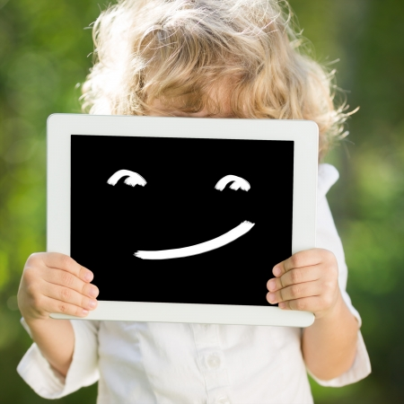 Child holding tablet PC with smile  Communication concept photo