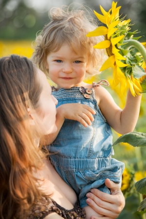 Child with sunflower in spring field photo