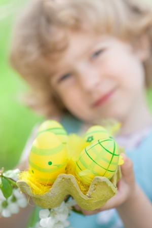 Happy child holding Easter eggs against spring green background photo