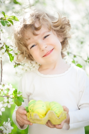 Happy child holding Easter eggs against spring flower background photo