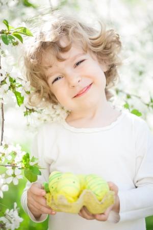 pascuas navide�as: Ni�o feliz que sostiene los huevos de Pascua contra el fondo flor de primavera