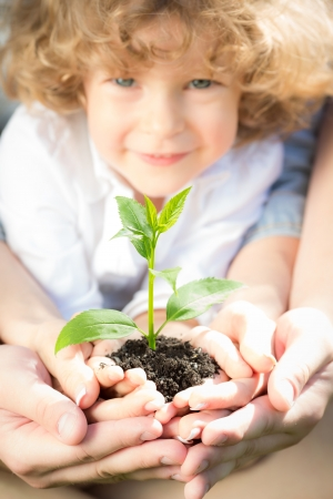 Family holding young green plant in hands. Ecology concept Stock Photo - 17642628