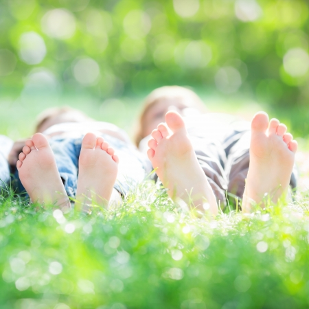 boy feet: Family lying on green grass in spring park