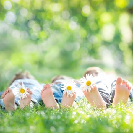 familie: Gezin met daisy bloemen liggend op het groene gras tegen de lente achtergrond wazig