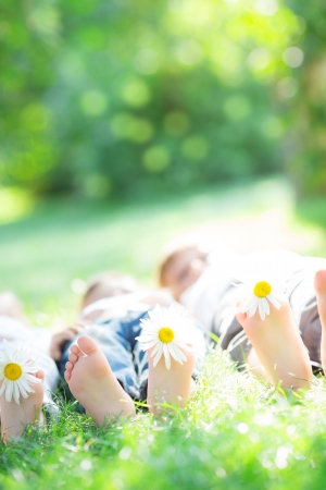 feet relaxing: Happy family lying on green grass outdoors in spring park