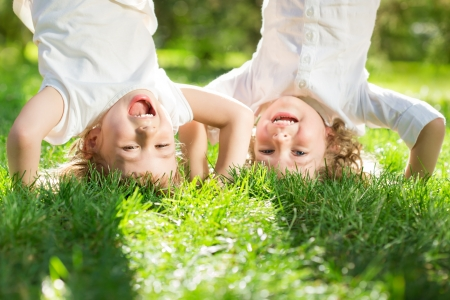children: Счастливые дети, играя кубарем на зеленой траве в парке весной