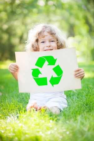 hands holding tree: Child holding paper with recycle symbol against green spring background. Ecology concept Stock Photo