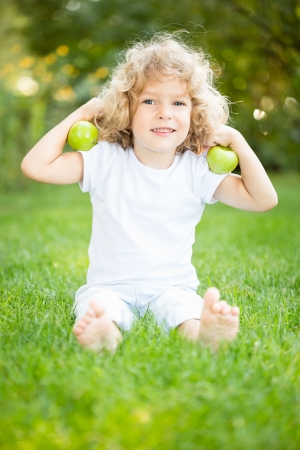 Happy child playing with apples on green grass in spring park photo
