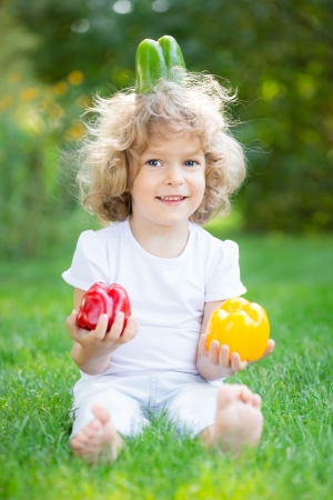 Happy child playing with vegetables on green grass outdoors in spring park photo