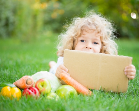 Happy child with fruits and vegetables holding paper blank against green spring background