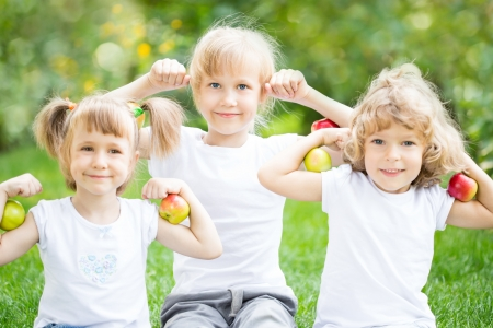 Happy children with apples against spring green background. Fitness concept photo