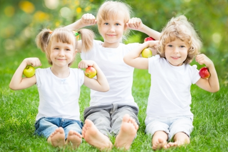 Happy children with fruits sitting on green grass in spring park photo
