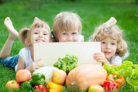 child food: Group of happy children with fruits and vegetables outdoors in spring park