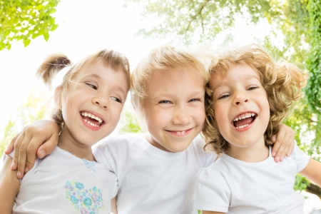 angle view: Low angle view portrait of happy children laughing outdoors in spring park. Fisheye shot Stock Photo