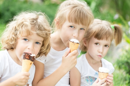 kids eating healthy: Happy friends eating ice-cream outdoors in spring park