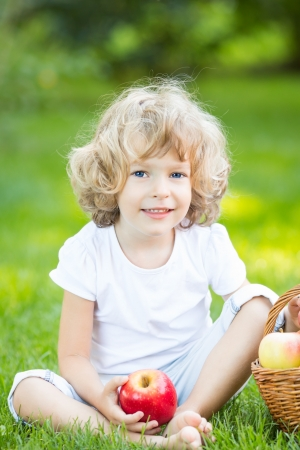 Happy child having picnic outdoors in spring park photo