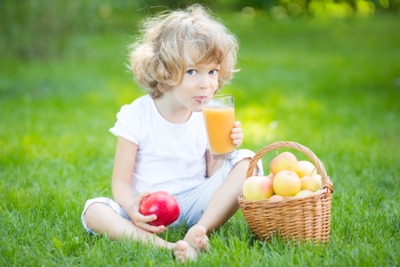 Happy child drinking apple juice in spring park photo